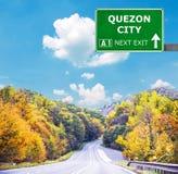 Panneau routier de QUEZON CITY contre le ciel bleu clair photographie stock