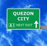 Panneau routier de QUEZON CITY contre le ciel bleu clair images stock