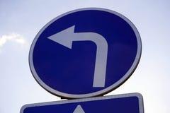 Panneau routier de virage à gauche au-dessus de ciel bleu images libres de droits