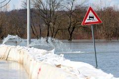 Panneau routier inondé de bande non stabilisée à côté de la protection d'inondation de barrières de boîte images stock