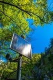 Panneau solaire ensoleillé dans la forêt Photo libre de droits