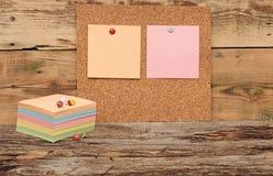 Panneau vide de liège avec les papiers de note colorés de pile Photographie stock libre de droits