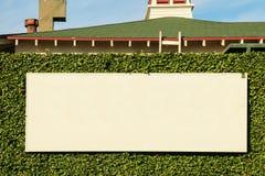 Panneau vide pour des annonces sur un mur couvert de lierre Image stock