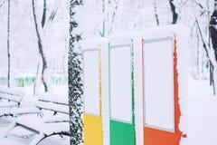 Panneaux d'affichage vides vides en parc public d'hiver Supports de couleur pour la publicité et arbres couverts de neige et banc images libres de droits