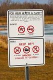 Panneaux d'avertissement autour d'étang de drainage de tempête photos libres de droits