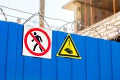 Panneaux d'avertissement et barbelé sur la barrière à la construction s Photographie stock libre de droits