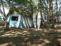Panneaux de ressac alignés contre une hutte de plage image stock