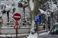 Panneaux routiers d'éléments avertissant et parking dans une ville neigeuse Images stock