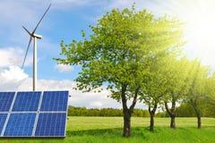 Panneaux solaires avec la turbine de vent sur le pré Photographie stock libre de droits