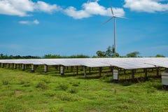 Panneaux solaires dans les fermes solaires avec le backgroun de ciel bleu de turbine de vent photos stock