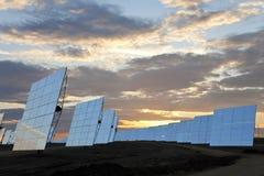 Panneaux solaires de miroir d'énergie renouvelable au coucher du soleil Image stock