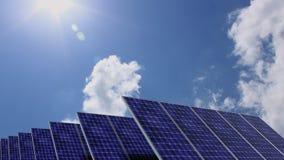 Panneaux solaires devant le ciel bleu avec le soleil lumineux Images stock