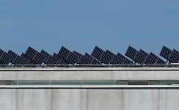 Panneaux solaires parfaitement alignés et inclinés pour recevoir l'énergie du soleil sur le toit d'un bâtiment Photographie stock