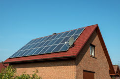 Panneaux solaires sur un toit rouge Images stock