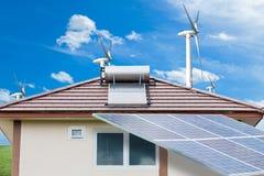 Panneaux solaires, turbines de vent sur l'herbe verte avec le backgrou de ciel bleu image stock