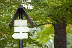 Panneaux vides de signe contre des arbres Image stock