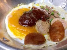 Panned egg. Fried eggs, sausage, pork chop served with oil in baked bread and coffee Royalty Free Stock Photo