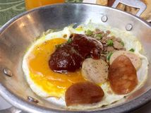 Panned egg. Fried eggs, sausage, pork chop served with oil in baked bread and coffee Royalty Free Stock Images