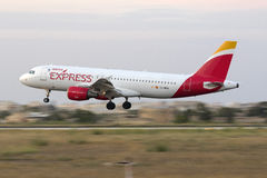 Panned shot of an Airbus landing. Luqa, Malta - 23 June 2016: Iberia Express Airbus A320 [EC-MEH] landing after sunset Royalty Free Stock Photography