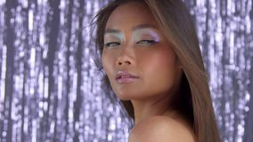 Thai asian model in studio with silver rain disco background and party makeup. Panned video of asian model on silver rain background wears party holographic stock video