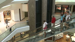 Panned view of elevators and escalators within mall. A view or scene of Shopping stock footage