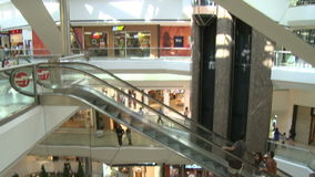 Panned view of shoppers in mall near escalators and elevators. A view or scene of Shopping stock footage