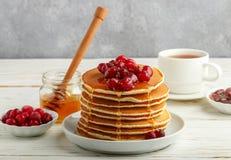 Pannekoek met honing en verse bessen Amerikaanse veenbes, vossebes stock afbeelding