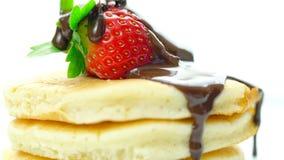 Pannekoeken met aardbei en gemotregend met chocoladesaus, macroclose-up stock afbeeldingen