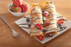 Pannekoeken met aardbeien, bosbessen en chocolade worden gediend die Royalty-vrije Stock Afbeelding