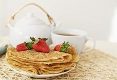 Pannekoeken met een aardbei en een hete thee in de theepot en de kop Royalty-vrije Stock Fotografie