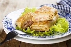 Pannekoeken met ham en kaas worden gevuld die stock afbeeldingen