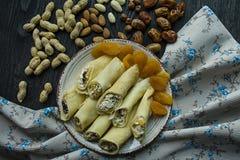 Pannekoeken met kwark, gedroogde pruimen, droge abrikozen en rozijnen Mening van hierboven Donkere houten achtergrond stock foto's