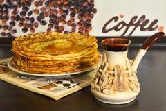 Pannekoeken op een plaat en een ceramische jezve met koffie Royalty-vrije Stock Afbeelding