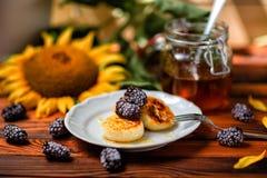 Pannekoeken van kwark met honing worden met bessen en zonnebloemen op een houten achtergrond wordt verfraaid gemaakt die stock foto