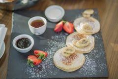Pannekoeken voor ontbijt met verse die aardbeien en een banaan met gepoederde suiker wordt bestrooid, en drie verschillende sause Royalty-vrije Stock Foto's