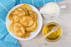 Pannekoeken in witte glasplaat, kruikmelk en honing Stock Afbeeldingen