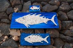 Pannelli di legno con i pesci che appendono sulle rocce nere Immagini Stock Libere da Diritti