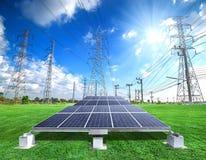 Pannelli a energia solare e pilone ad alta tensione di elettricità Immagine Stock