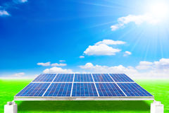 Pannelli a energia solare sul campo di erba verde contro il bello cielo Fotografie Stock Libere da Diritti