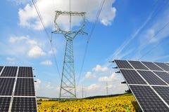 Pannelli solari con i piloni di elettricità nel giacimento del girasole immagine stock