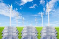 Pannelli solari e generatore eolico sul campo di erba verde contro il blu Fotografia Stock