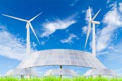 Pannelli solari e generatore eolico sul campo di erba verde contro il blu Fotografie Stock