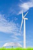 Pannelli solari e generatore eolico sul campo di erba verde contro il blu Immagini Stock