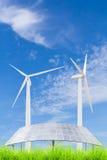 Pannelli solari e generatore eolico sul campo di erba verde contro il blu Fotografia Stock Libera da Diritti
