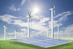 Pannelli solari, generatori eolici su erba verde con il backgrou del cielo blu immagini stock libere da diritti