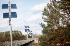 pannelli solari nel ponte della foresta e fiume in primavera ecologia immagini stock