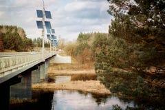pannelli solari nel ponte della foresta e fiume in primavera ecologia fotografia stock libera da diritti