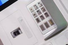 Pannello anteriore di BANCOMAT con una tastiera per entrare in una parola d'ordine, in un analizzatore dell'impronta digitale ed  Fotografie Stock