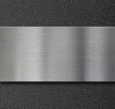Pannello del metallo sopra il piatto di plastica nero Immagine Stock