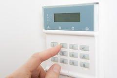 Pannello di controllo della regolazione della donna sul sistema di sicurezza domestico Fotografia Stock